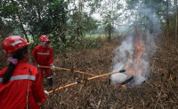 Practicing using equipment to put out flames during a fire drill, Indonesia. Achmad Ibrahim (CIFOR)